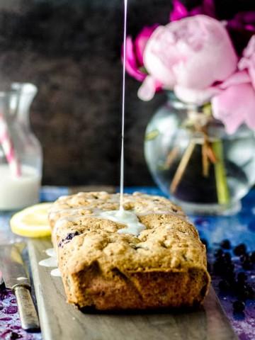 pouring lemon glaze on a lemon blueberry cake