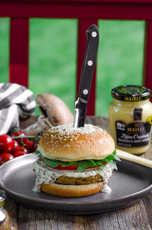 Side view of a grill able veggie burger with a knife on top
