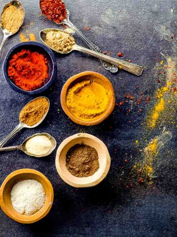 Bowls and spoons with spices for shawarma spice mix