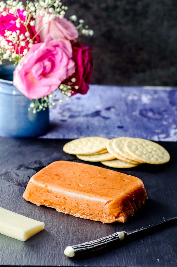 Dulce de membrillo on a black serving board with some crackers in the background