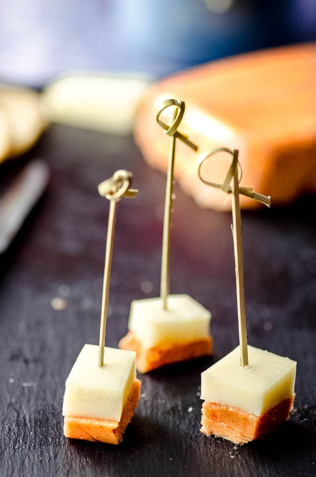 Three Spanish tapas of dulce de membrillo and manchego cheese on a tooth pick