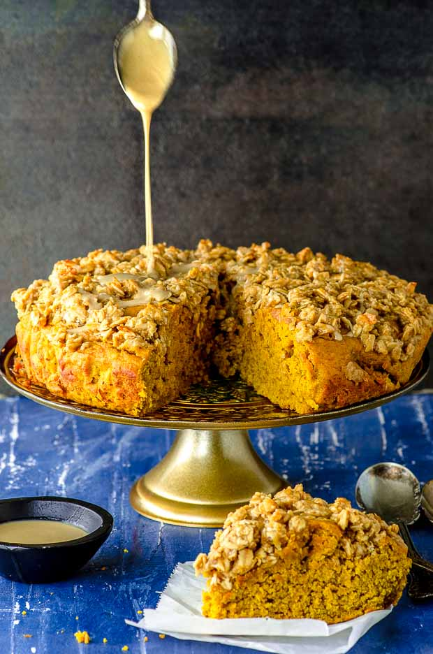 Drizzling a sweet tahini sauce on our pumpkin coffee cake. Pumpkin coffee cake is on a cake stand