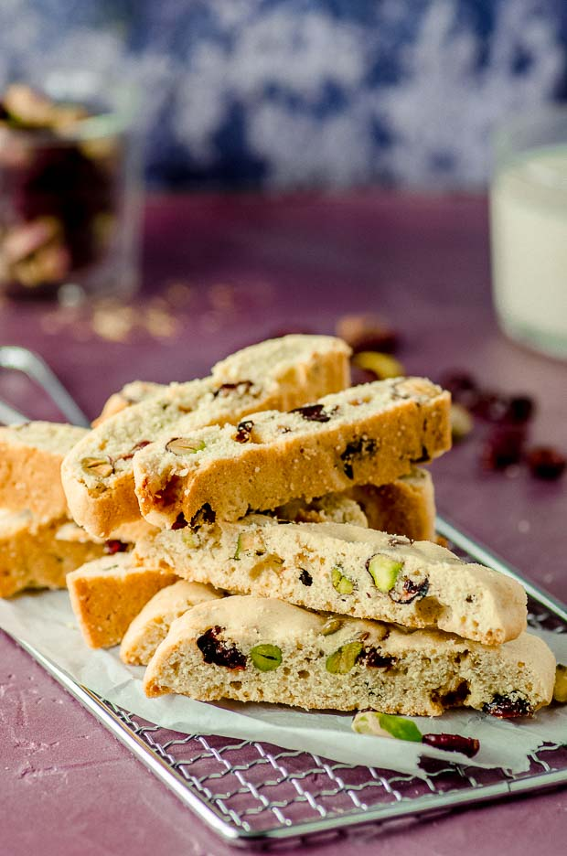 A pile of cranberry pistachio biscotti on a wire cooling rack