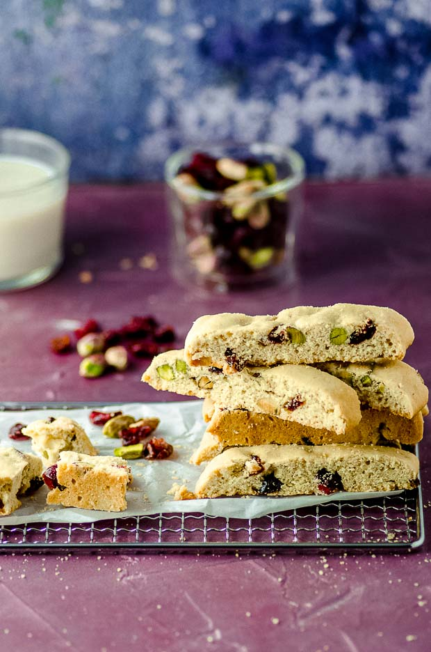 Side view of a bunch of cranberry pistachio biscotti on a wire cooling rack