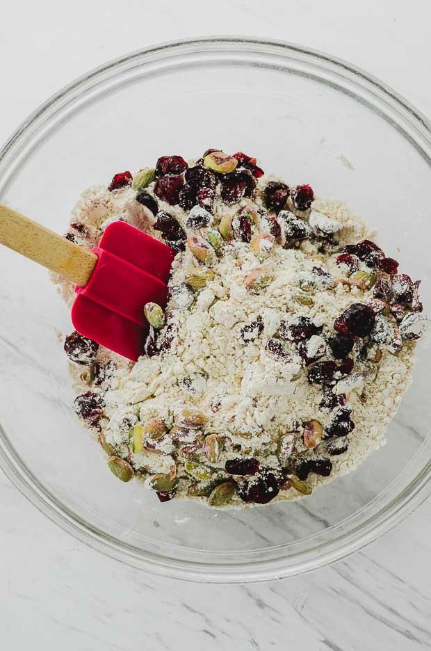A clear bowl with flour, baking powder, salt, cranberries and pistachios