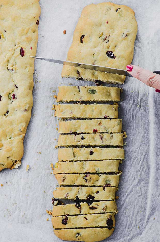 cutting cranberry pistachio baked biscotti dough cooled