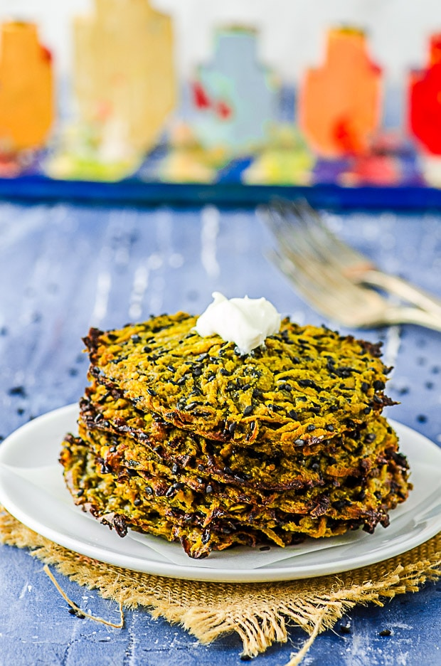 Butternut squash Latkes staked on a white plate with a Menorah in the background