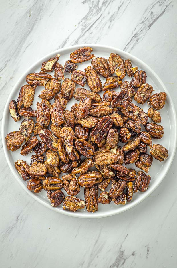 Bird's eye view of a round plate filled with candied pecans