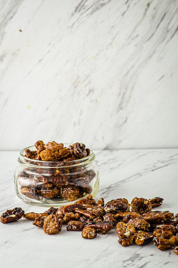 Side view of a clear glass jar filled with candied pecans