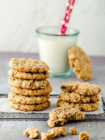 Two piles of peanut butter oatmeal cookies and a glass of milk in the background