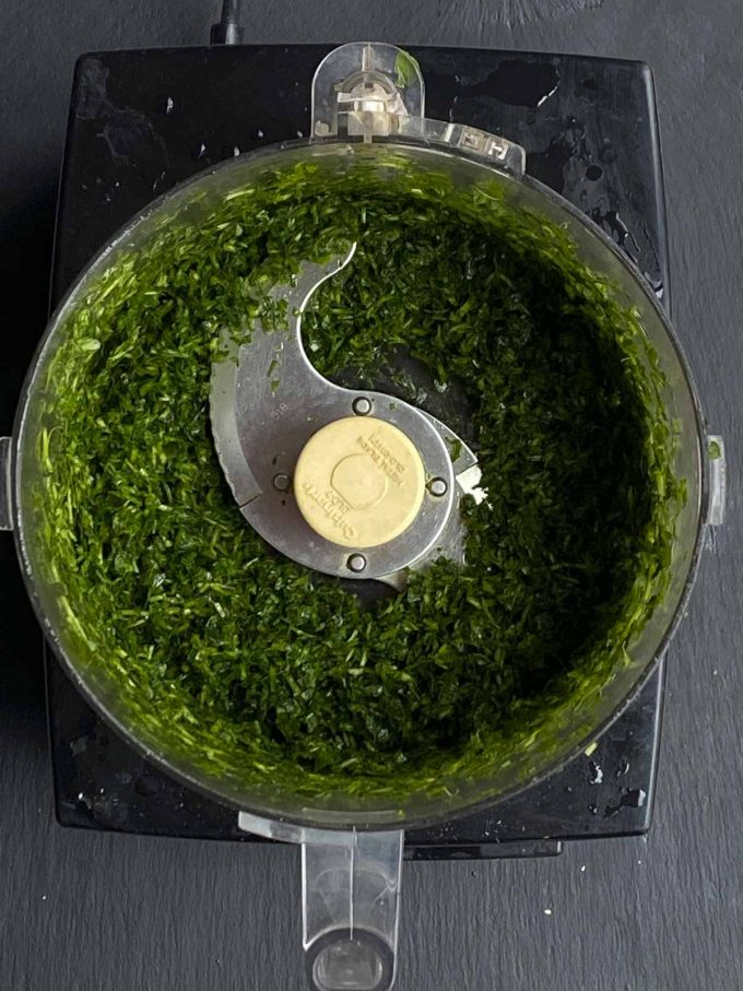 Chopped parsley in a food processor bowl