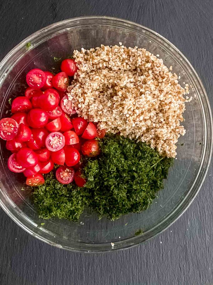 chopped parsley, soaked bulgur wheat and fresh tomatoes in a bowl ready to be mixed for tabouli salad