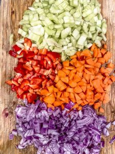 Diced celery, red pepper, carrots and onions in a wood cutting board ready to make black bean soup