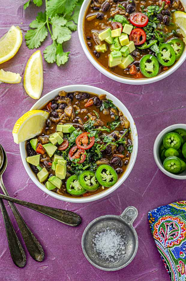 Bird's eye view of two white bowl filled with black bean soup and topped with jalapeño slices and diced avocado