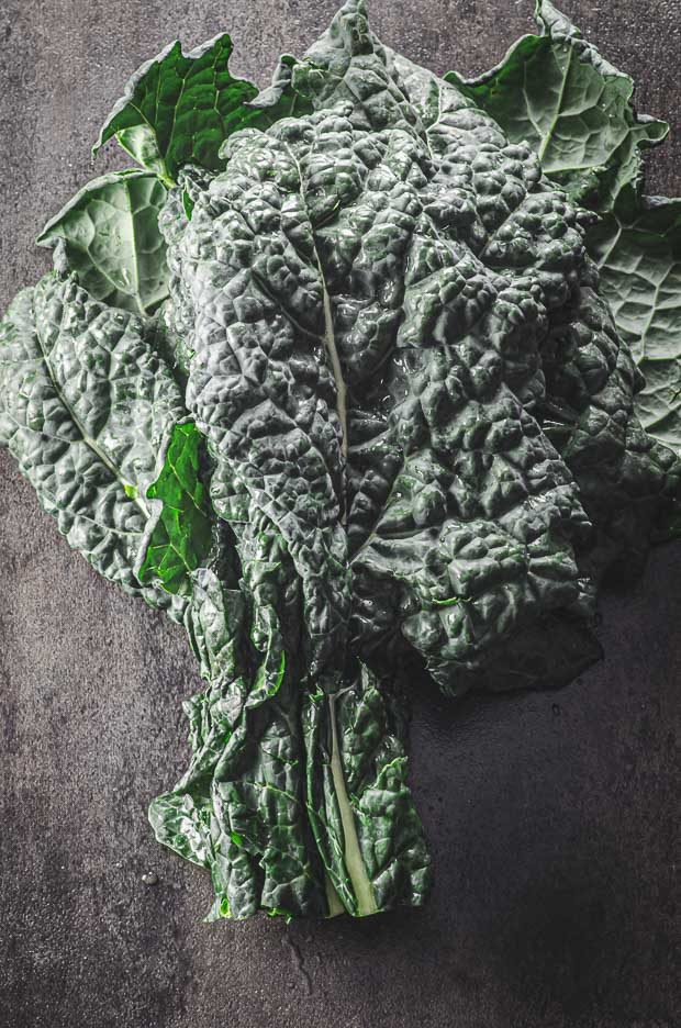 one bunch of Tuscan kale on a black surface