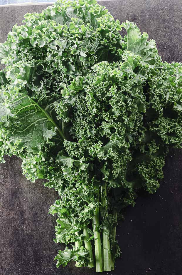 One bunch of kale con a black surface