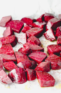 Raw cut beets on a baking sheet lined with parchment paper ready to be cooked