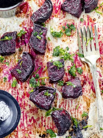 Bird's eye view of a baking sheet with cut roasted beets and a small bowl will flaky salt