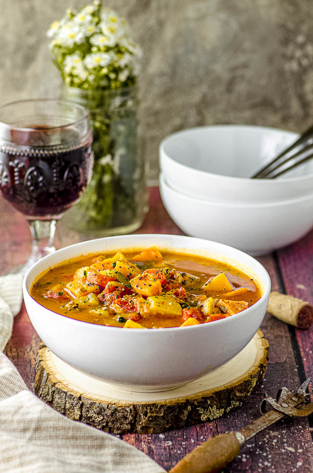 side view of a white bowl filled with vegetable soup with a glass of red wine in the background