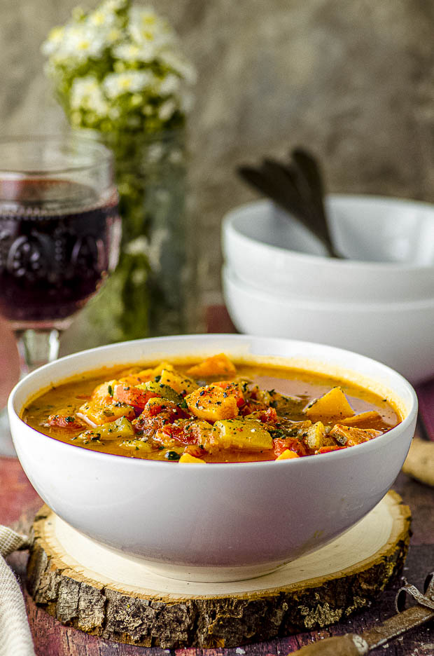 Close up side view of a white bowl filled with vegetable soup with a glass of red wine in the background