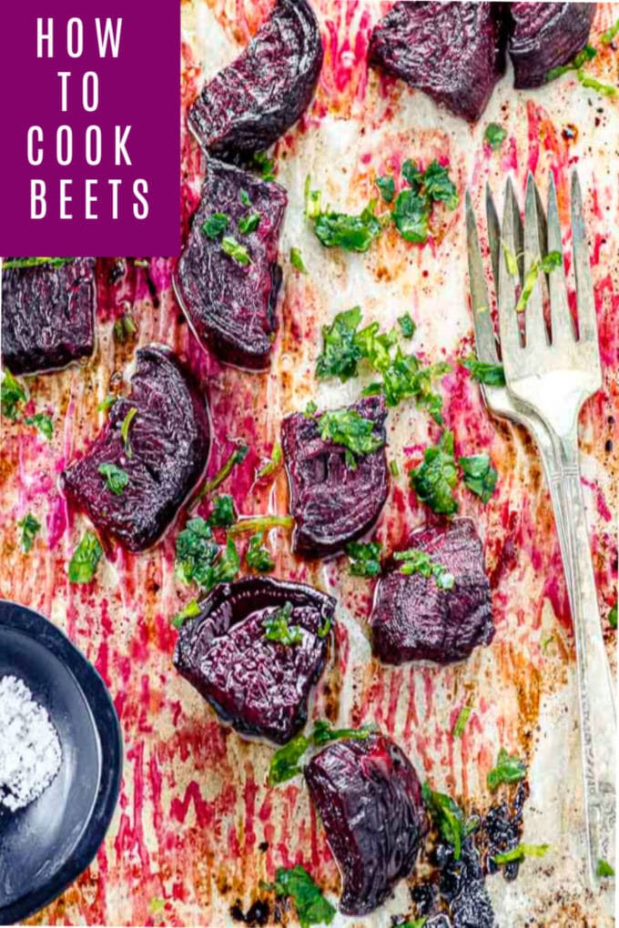 Bird's eye view of a baking sheet with cut roasted beets and a small bowl will flaky salt.