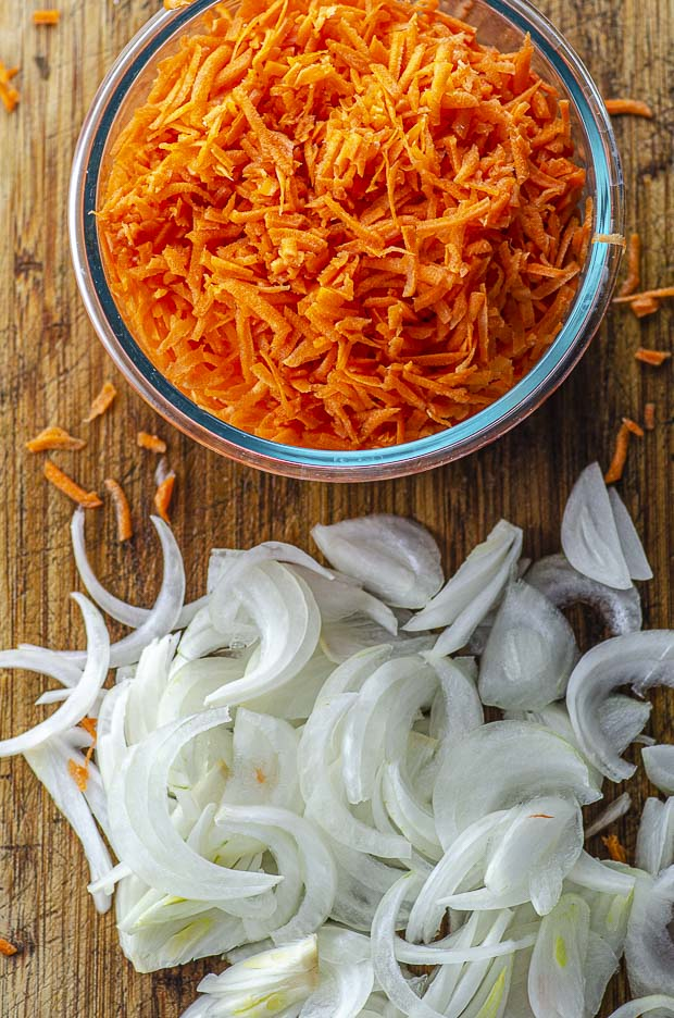Bird's eye view of a bowl with shredded carrots and some slices onons