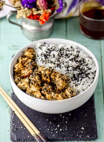 Side view of a white bowl with tahini-miso eggplant rice bowl