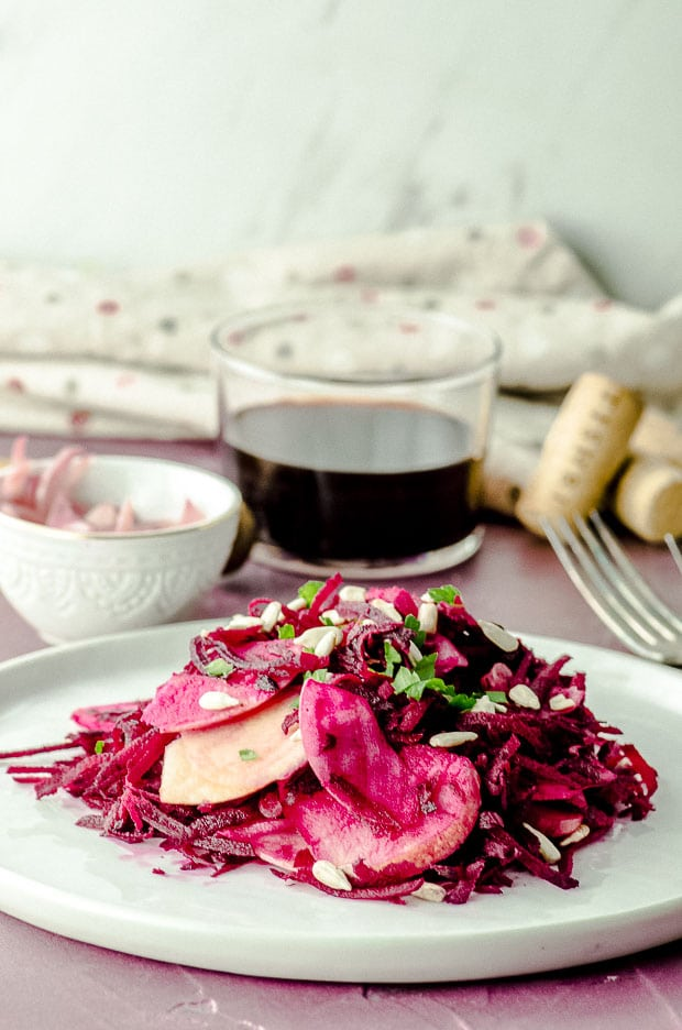Side view of a plate with raw beet salad topped with sunflower seeds and parsley