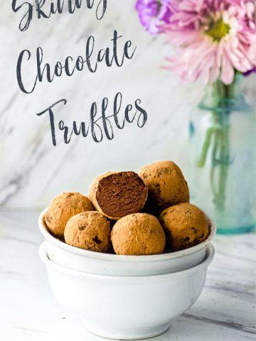Side view of two staked bowls filled with dark chocolate truffles with a vase with flower in the background with a sign reading skinny chocolate truffles