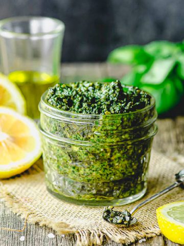 side view of a small mason jar filled with pesto with some lemons and olive oil in the background