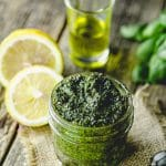 45 degree angle view of a small mason jar filled with pesto with some lemons and olive oil in the background