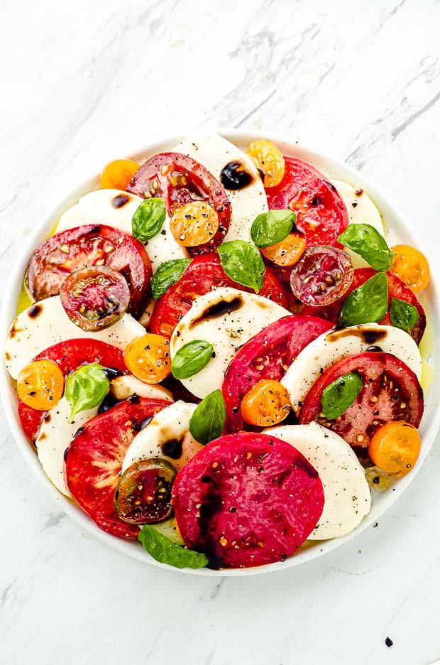 Bird's eye view of a Caprese salad with tomatoes, mozzarella and basil