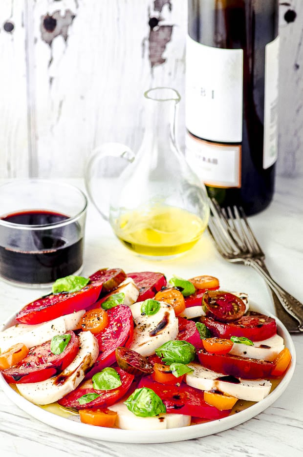 Side view of a white plate with Caprese Salad with a bottle of wine on the background