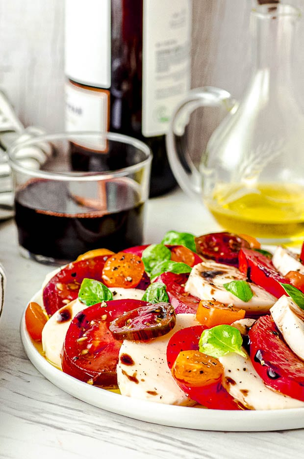 Side View of a Caprese Salad with a bottle of red wine on the background