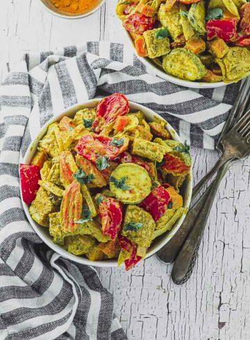 Bird's eye view of a bowl of tempeh and veggies with tahini and turmeric sauce.
