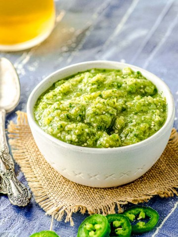 45 degree angle view of a white bowl filled with tomatillo salsa verde