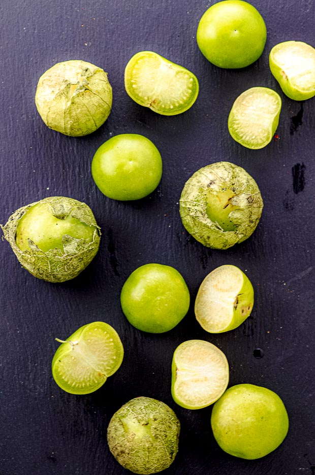 fresh tomatillos on a black surface