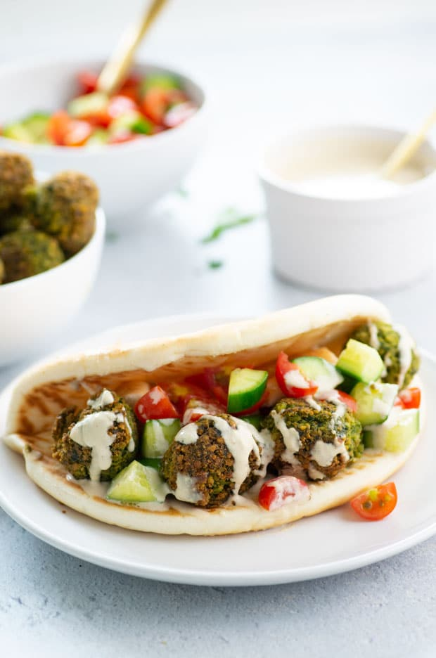 Side view of a falafel sandwich dripping with tahini sauce