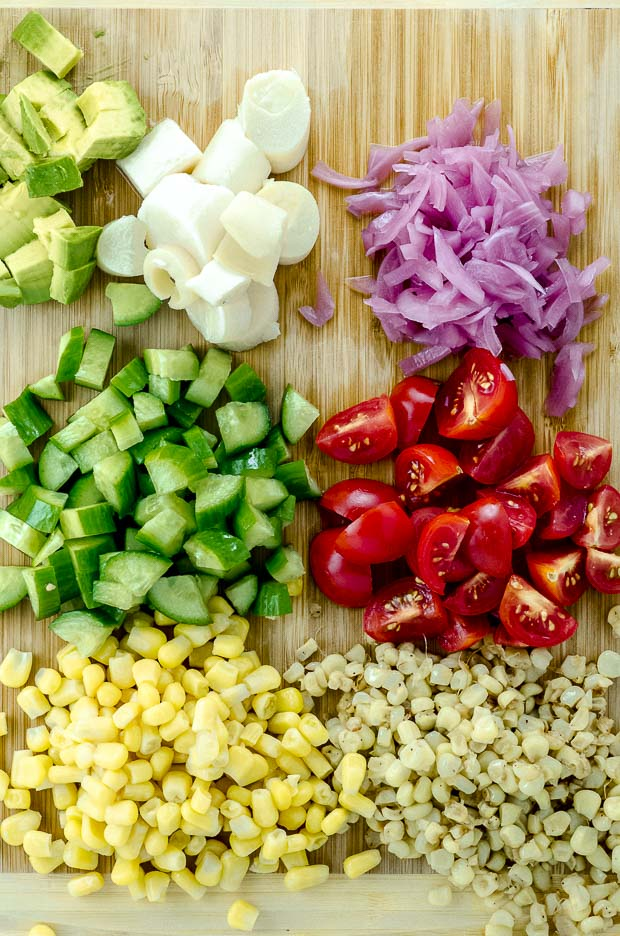 Diced corn, tomatoes, cucumbers pickled onions, avocado and hearts of palm on a wood cutting board