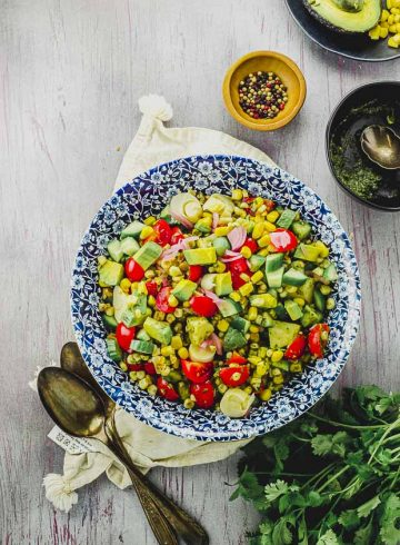 bird's eye view of a blue flowered plate filled with avocado corn salad