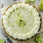 Bird's eye view of a key lime pie tart with key lime around the tart