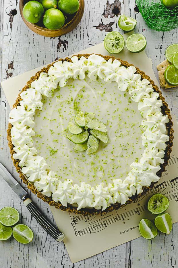 Bird's eye view of a key lime pie tart with key lime around the tart
