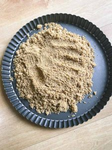 graham cracker crumbs in a tart pan mold
