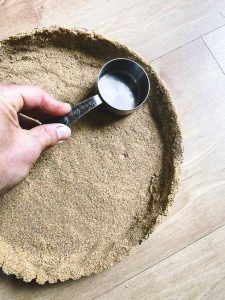 Pressing graham crackers into a pie crust