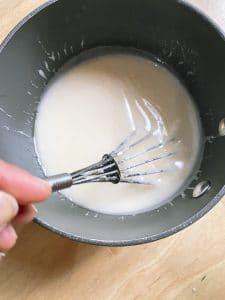 Whisking vegan key lime pie filling in a saucepan