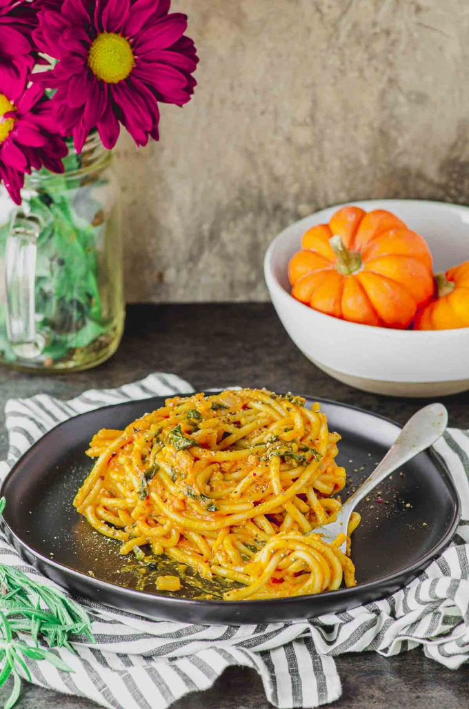 Side view of a plate of spaghetti with pumpkin pasta sauce and a bowl with mini pumpkins on the background