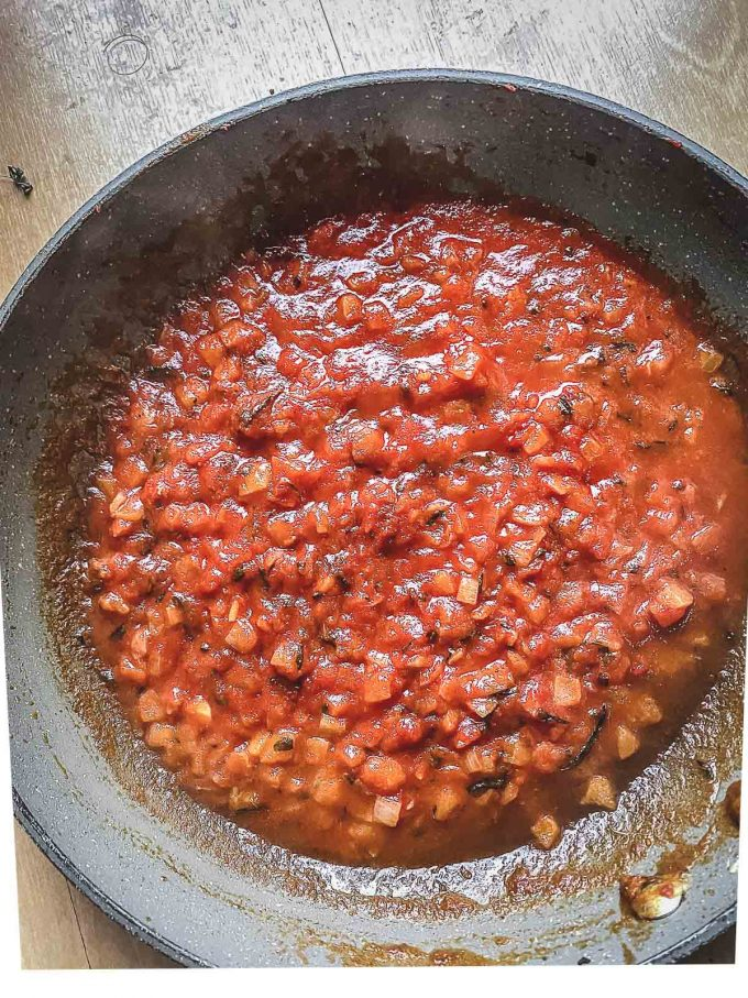 Adding tomato paste to a skillet with onion, ginger and herbs