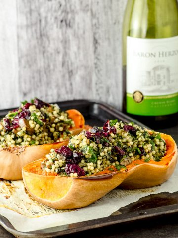 Side view of two roasted butternut squash halves stuffed with Israeli couscous and topped with dried cranberries
