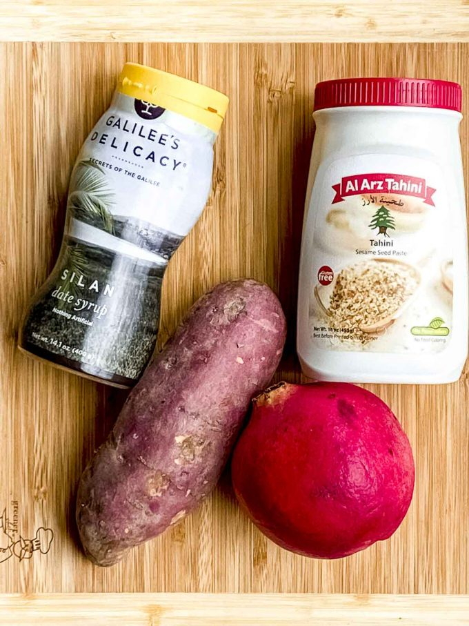 The ingredients for this sweet potato recipe on a wood board. Sweet potatoes, tahini, silan and pomegranates