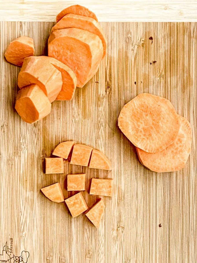 Sliced and cubed uncooked sweet potatoes on a wood board